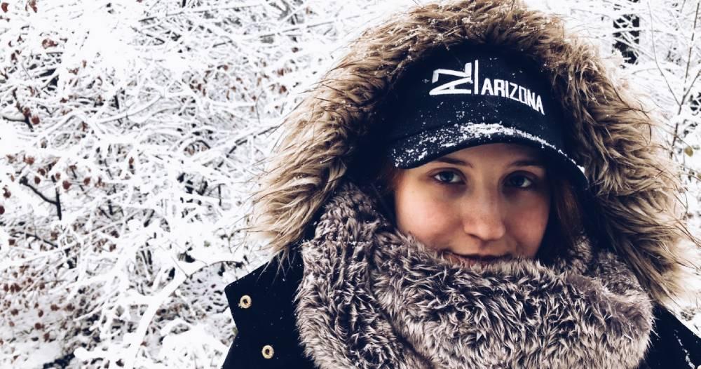 Marina mit Schal und Kapuzenjacke in einer Schneelandschaft