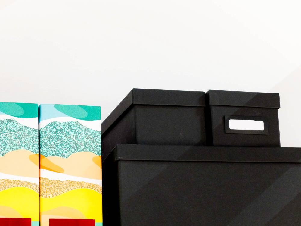 Schwarze Boxen und bunte Ordner in Nahaufnahme