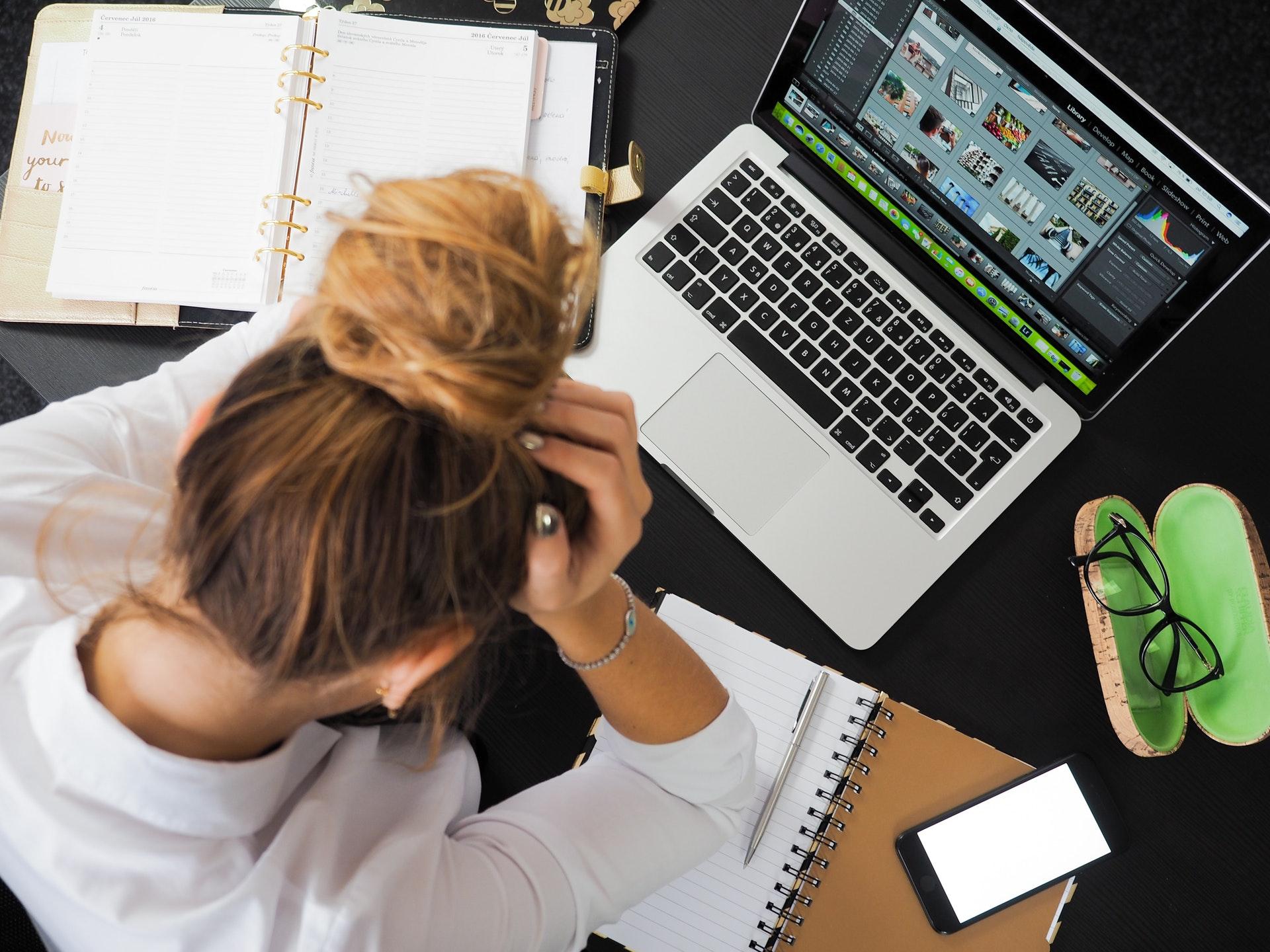 Frau, die verzweifelt über ihren Laptop und ihr Notizbuch lehnt