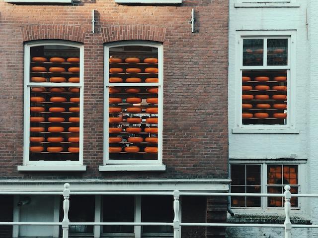 Blick auf drei Fenster: Mehrere dutzend Käseräder liegen auf Regalen direkt vor Fenstern